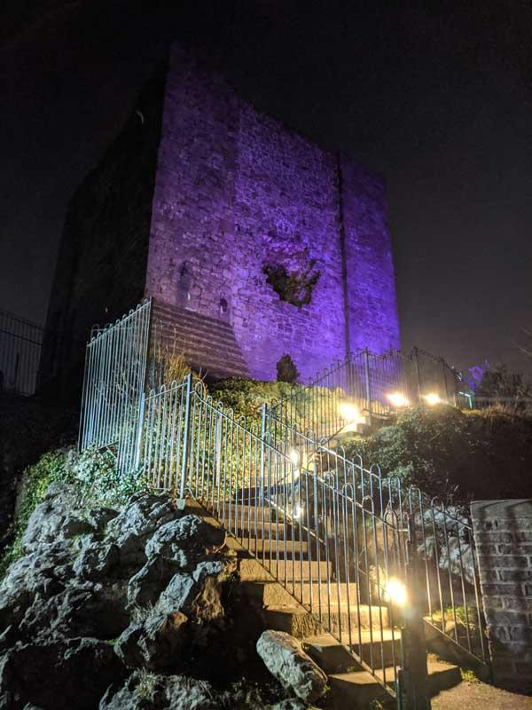 Clitheroe Castle lit up in purple at night